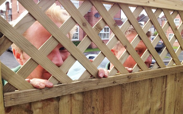Kevin and Martyn from Frosts peering through fence on set of Love Your Garden