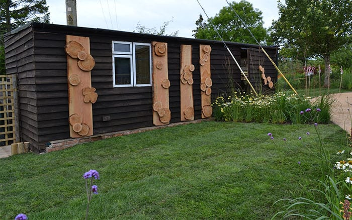 black-shed-with-log-insect-habitats-love-your-garden