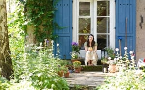 woman-sitting-on-doorstep-in-garden-plants-borders
