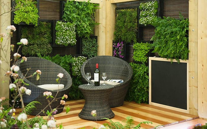 Contemporary woodland garden with rattan seating and wall planters - great garden design ideas from the Young Gardeners of the Year competition