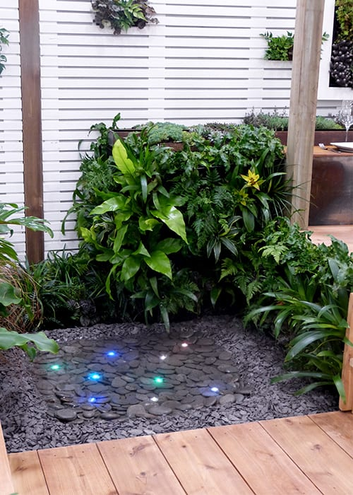 Capel Manor College water feature in yoga garden with lights underneath a still pool on slate chips and cobbles