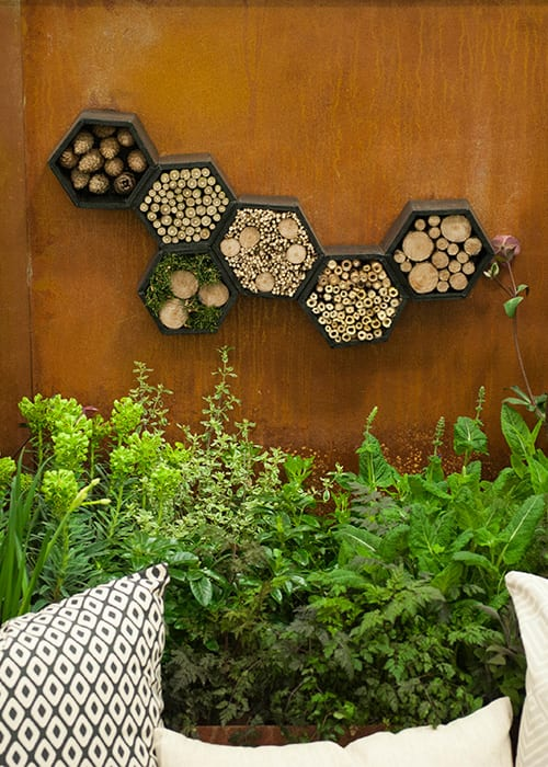 Pershore College show garden Path to Discovery, including hexagonal insect hotels on the rusty corten steel wall