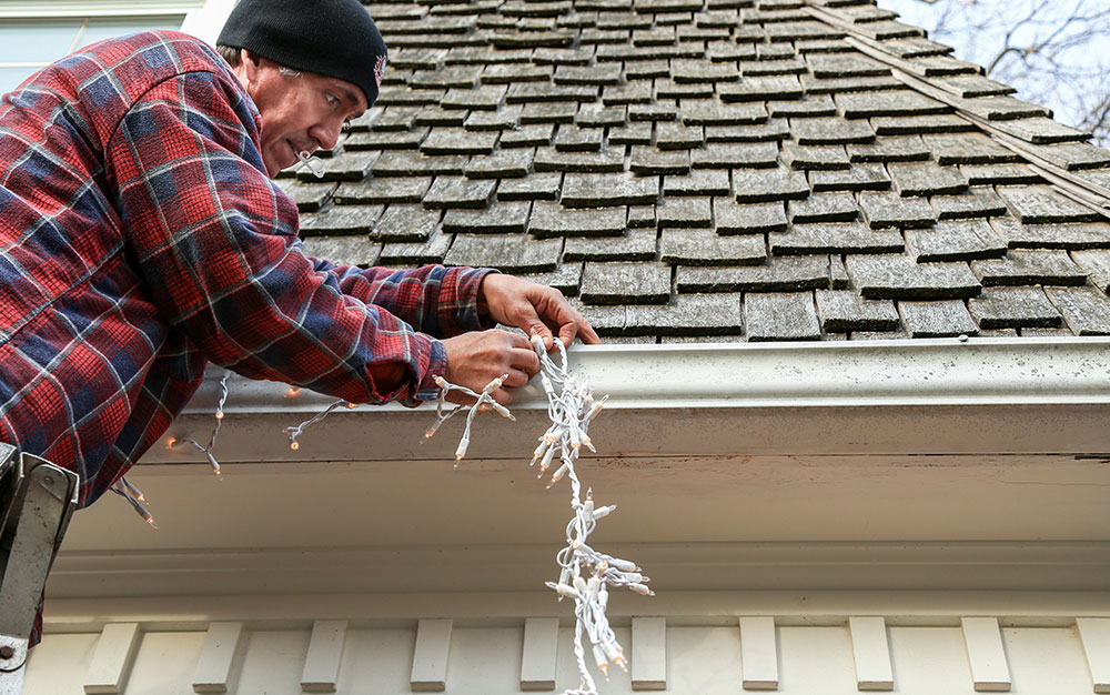 man putting up outdoor Christmas lights