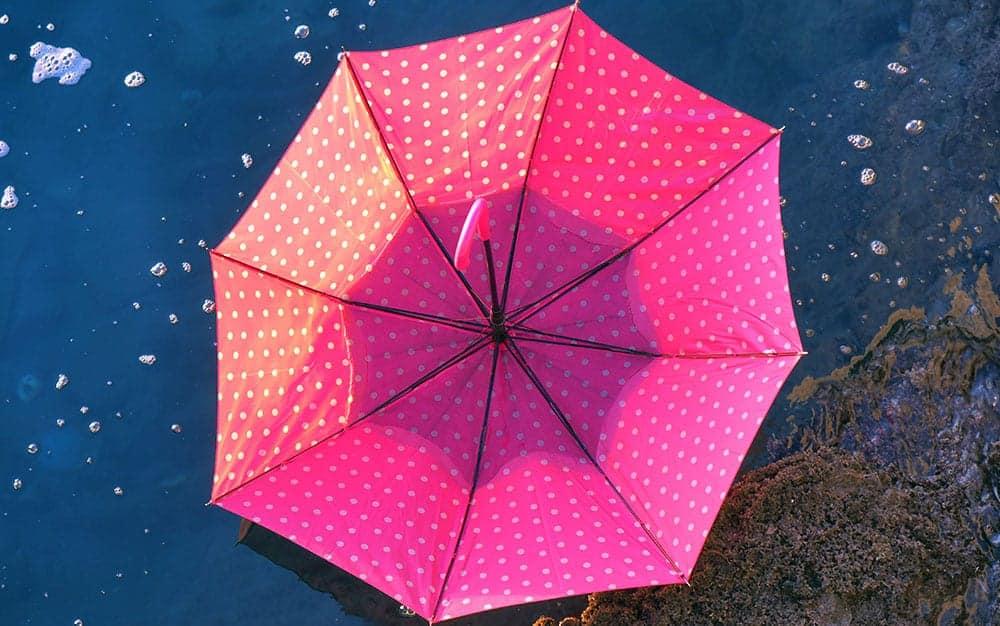 Upturned-pink-umbrella-on-ground